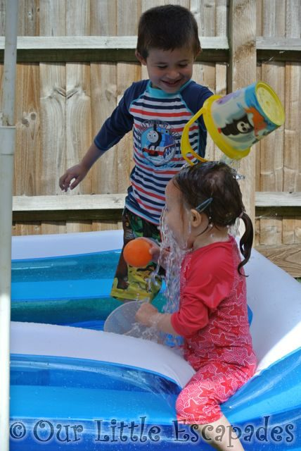 ethan pouring bucket water over little es head