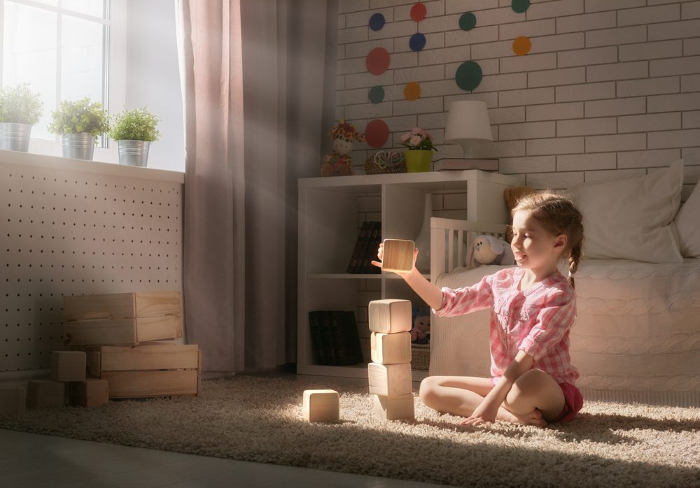 girl playing wooden building blocks