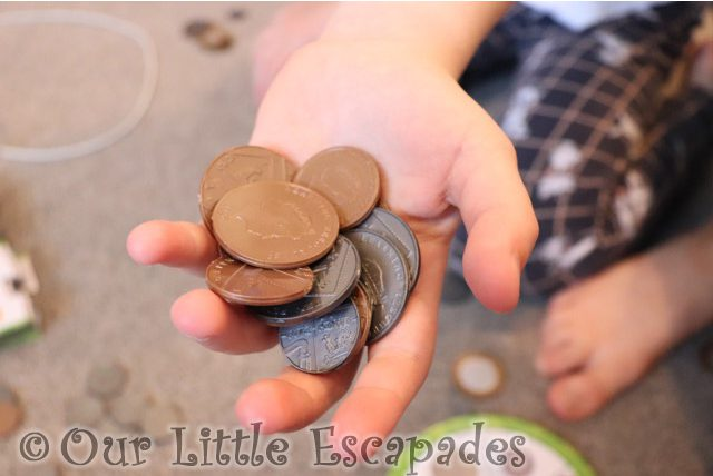 little es hand holding realistic plastic coins